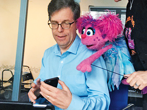 Michael Levine looking at a cell phone with muppet Abby Cadabby