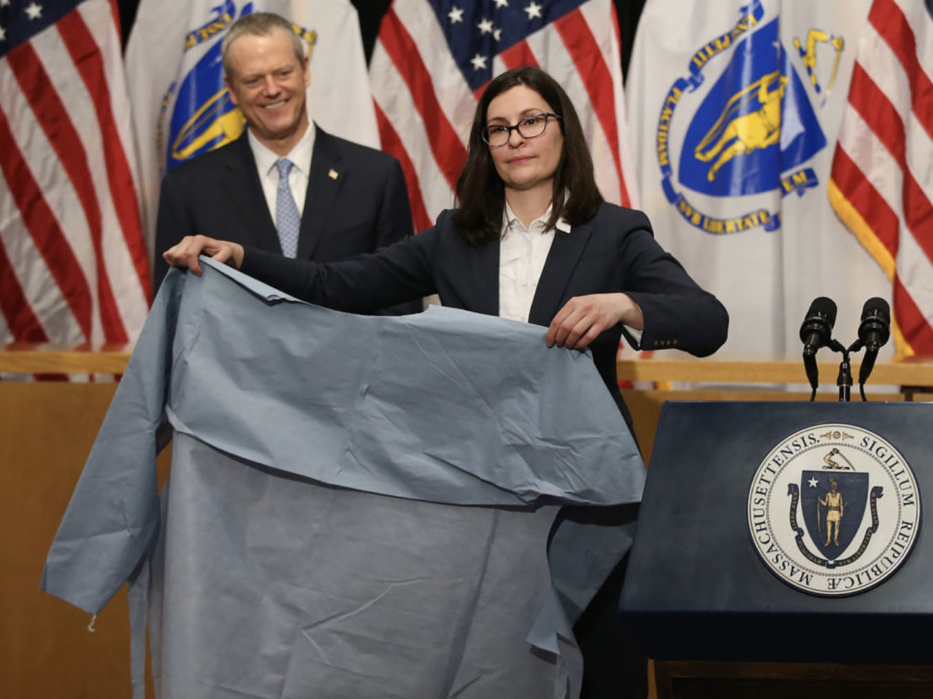 Brenna Schneider MBA'11 holds an isolation gown with Gov. Charlie Baker in the background